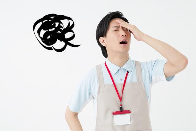 悩んでいる様子の男性介護士のイメージ