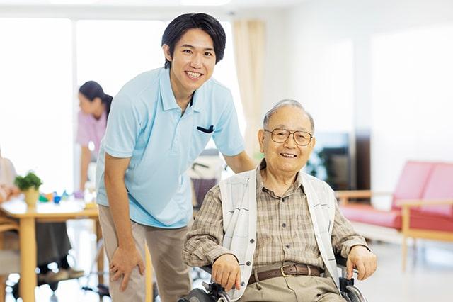 利用者と笑顔で接している男性介護士のイメージ