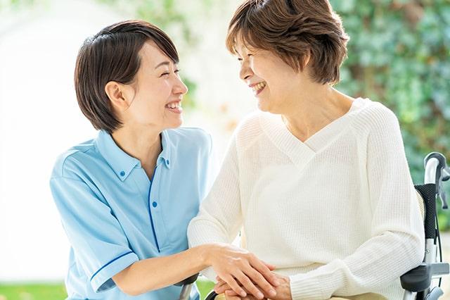 介護士と利用者さんが手を取り合って微笑んでいる様子