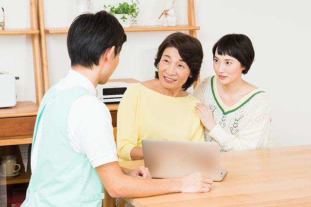 介護士が利用者さんとその家族の相談にのっているイメージ