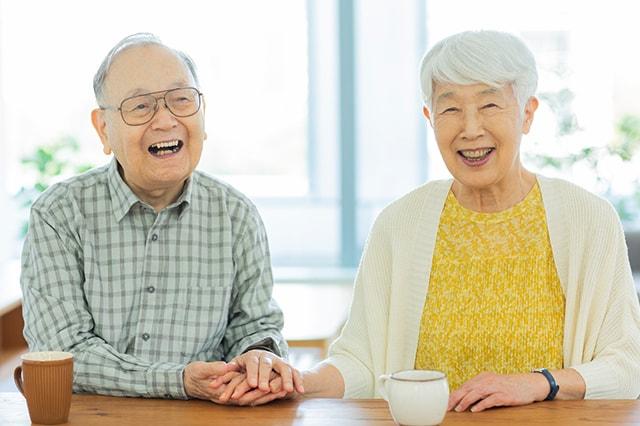 笑顔で手を取り合うシニア夫婦