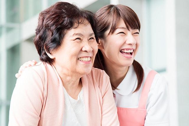 老健で笑顔で景色を眺めている入所者とスタッフのイメージ