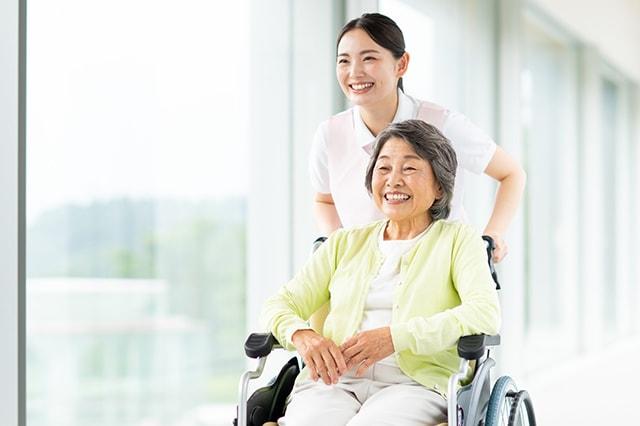 サービス提供責任者と車椅子に乗った利用者さまが歩いている様子