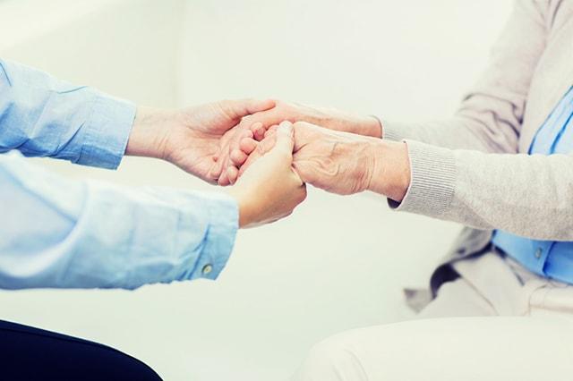 生活相談員・支援相談員(ソーシャルワーカー)と利用者様が手を取り合っているイメージ