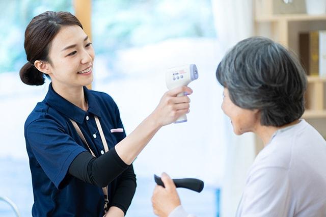 介護スタッフが利用者の体温検査をしている様子