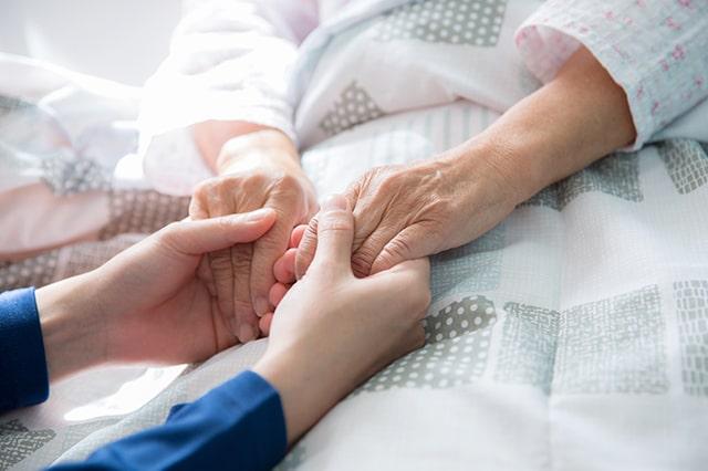 介護職員と利用者が手を取り合っている様子